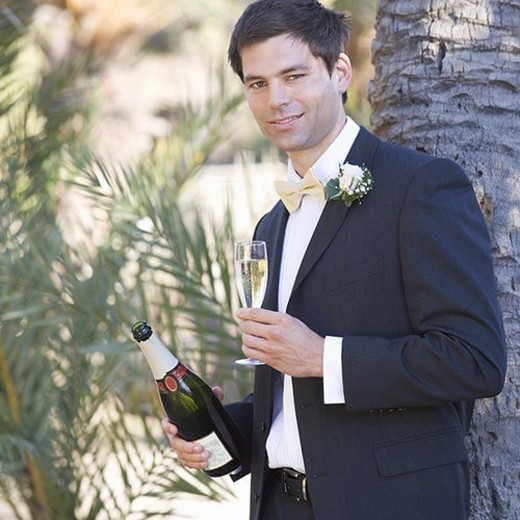 A groom drinking champagne : Stock Photo