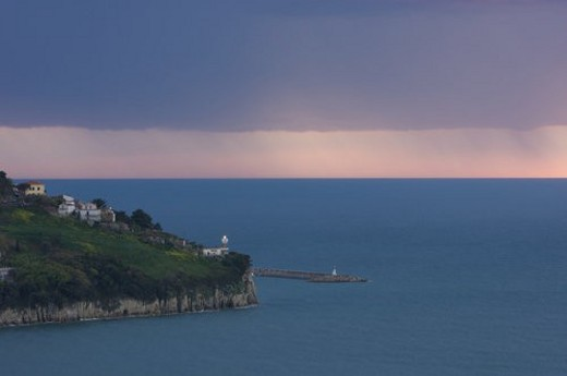 Agropoli lighthouse and harbour in approaching storm at dusk : Stock Photo