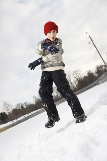 Caucasian boy with mouth open wearing sweater and red winter cap gesturing with arms and hands. : Stock Photo