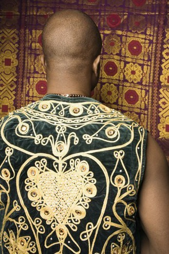 Rear view portrait of African-American mid-adult man wearing embroidered African vest. : Stock Photo