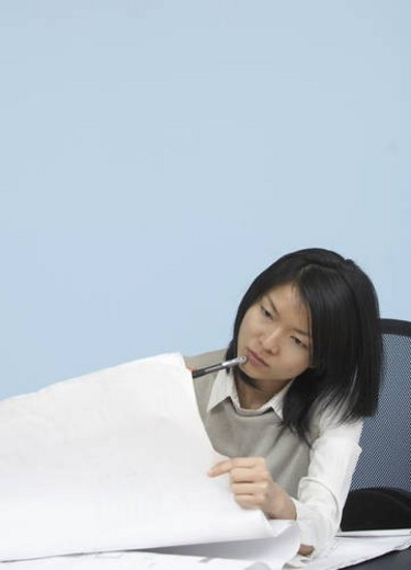 Mid-Adult Woman Looking at Blueprint : Stock Photo