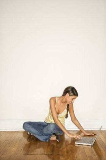 Stock Photo: 4029R-372025 Attractive Young Woman Smiling Sitting on Floor with Laptop