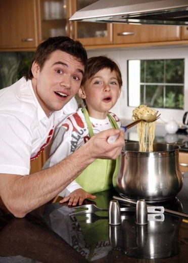 Father and son cooking spaghetti : Stock Photo