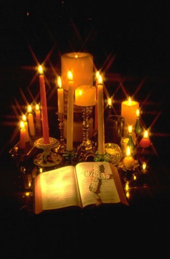 Candles surrounding open Bible with a cross on the pages : Stock Photo
