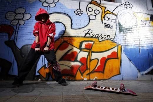 Young man and skate board in front of graffiti : Stock Photo