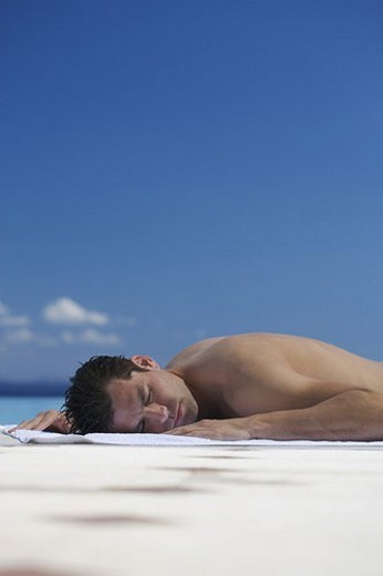 A man sunbathing by a pool : Stock Photo