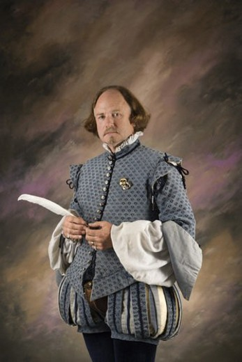 William Shakespeare in period clothing holding feather pen standing and looking at viewer. : Stock Photo