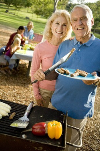 Stock Photo: 4029R-377240 Grandparents and family in park with barbeque