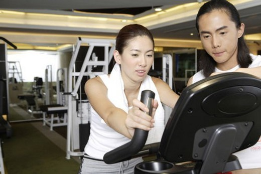 Stock Photo: 4029R-377382 Young man and young woman looking at screen of riding machine