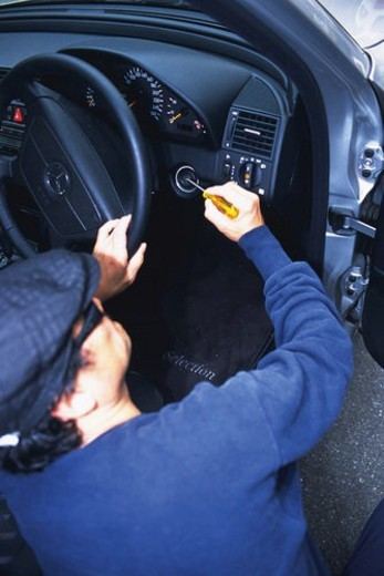 Burglar breaking into a car, High Angle View : Stock Photo