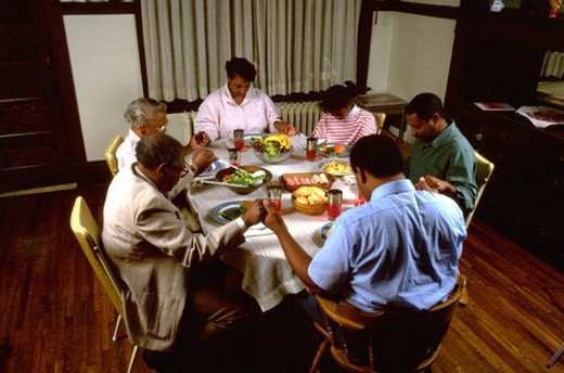 Stock Photo: 4029R-37815 Family of three generations saying grace at dinner table