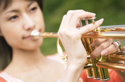 Stock Photo: 4029R-378319 Woman playing a trumpet