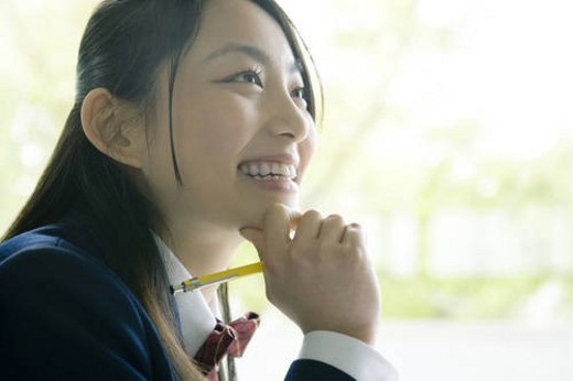 High school student in classroom, smiling : Stock Photo