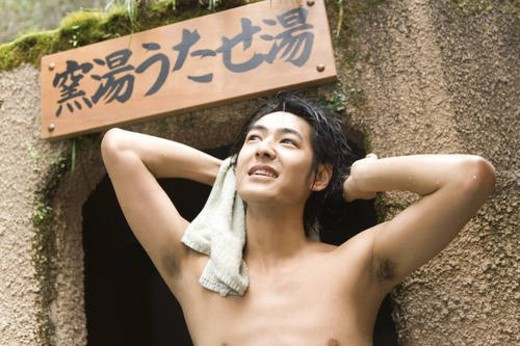 Naked man looking up and holding a towel, hot spring, front view, Japan : Stock Photo