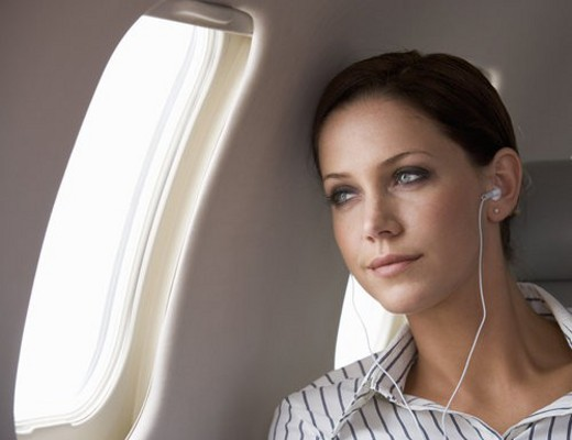 Stock Photo: 4029R-380861 A businesswoman listening to music on a flight