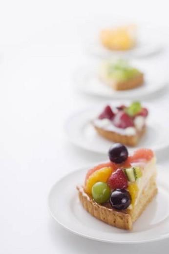 Pieces of tart on plates, white background : Stock Photo