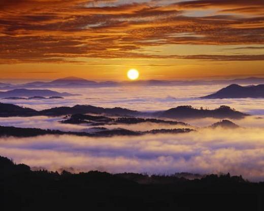 Fog shrouded mountain range at sunrise : Stock Photo