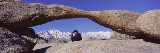 Photographer Joe Sohm with panoramic camera frames shot of Mount Whitney through Alabama Hills Arch in Alabama Hills : Stock Photo