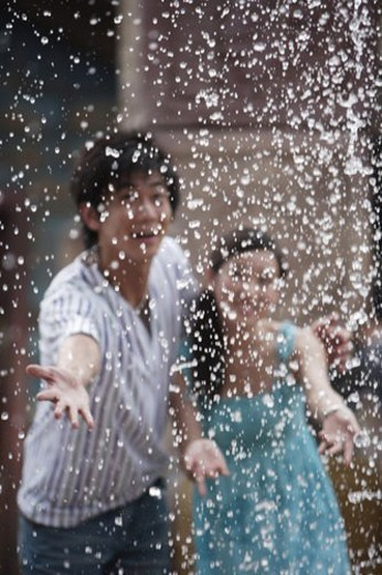 Young couple touching water beads downwards : Stock Photo