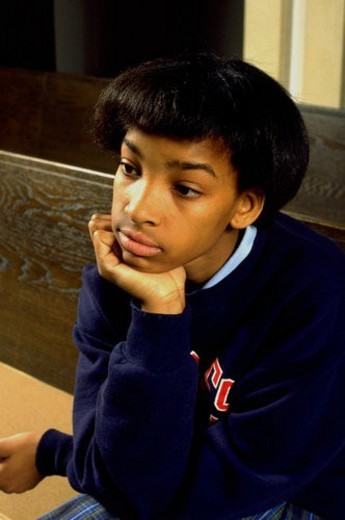 Girl age 13 thinking in church pew with chin in hand : Stock Photo