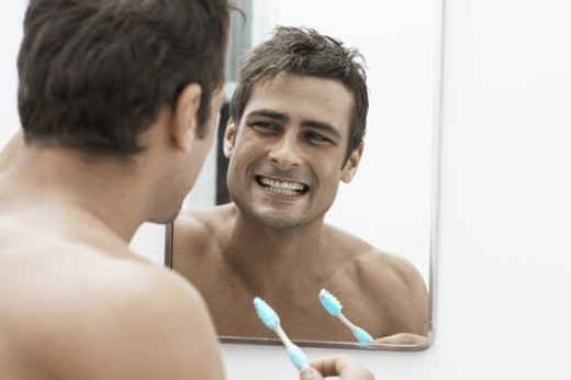 Stock Photo: 4029R-394698 Mid adult man cleaning teeth