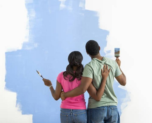 African American couple standing together looking at half-painted wall. : Stock Photo