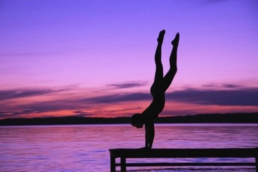 Stock Photo: 4029R-395005 A person in a hand stand on a dock against a sunset