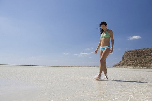 A woman walking on a beach : Stock Photo