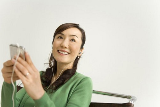Stock Photo: 4029R-396206 A Mature Adult Woman Listening to Music with a Portable Music Player, Low Angle View, Differential Focus, Copy Space