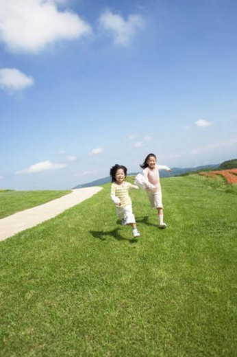Stock Photo: 4029R-397641 Brother and sister running through a park