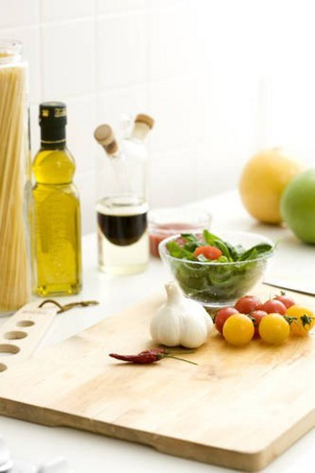 Chopping board with cherry tomatoes and garlic : Stock Photo