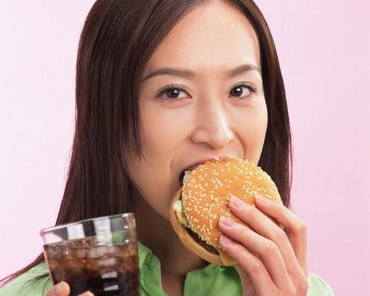 A Woman Eating Hamburger, Looking at Camera, Front View : Stock Photo
