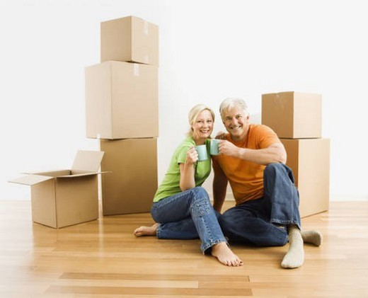 Stock Photo: 4029R-400252 Middle-aged couple sitting on floor among cardboard moving boxes with coffee.