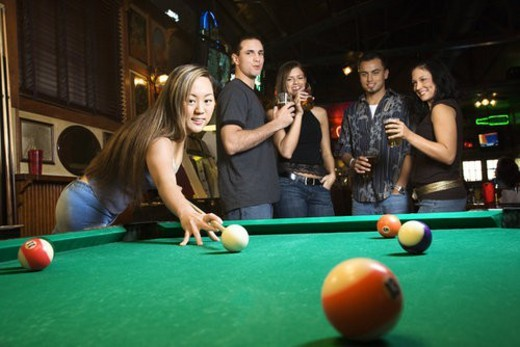 Young asian woman preparing to hit pool ball while playing billiards. : Stock Photo