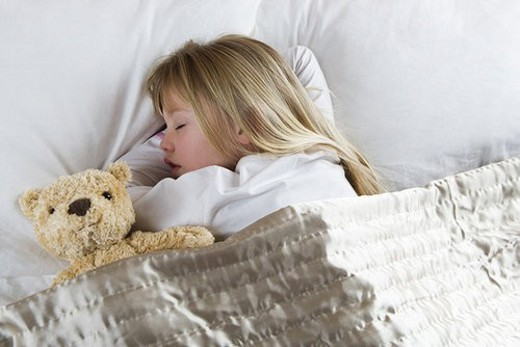 Young girl asleep in her bed with a teddy bear : Stock Photo