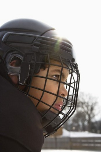 Close up of ice hockey player boy in cage helmet with look of concentration. : Stock Photo