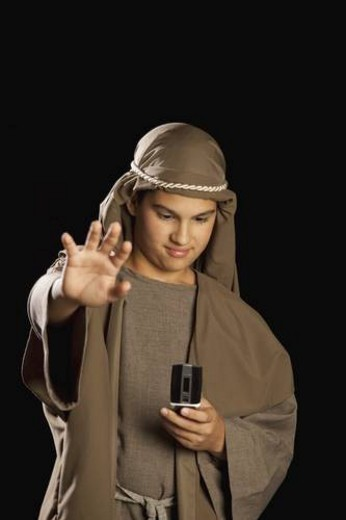 Stock Photo: 4029R-403653 boy depicting jesus holding a cellphone