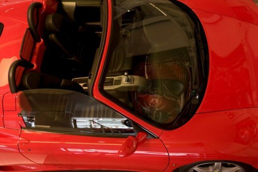 Stock Photo: 4029R-405847 Aerial view  from side, of red Ferrari sports car convertible, front detail showing seats and dash board