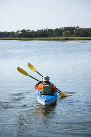 Stock Photo: 4029R-406941 Back view of African American middle-aged couple paddling kayak.