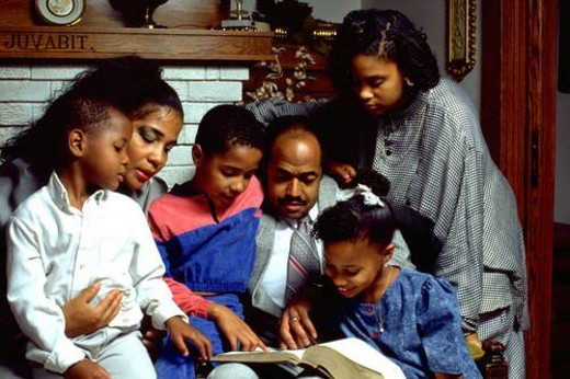 Stock Photo: 4029R-408152 African American family reading Bible in their home with children and parents