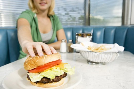 Stock Photo: 4029R-408710 Teenage girl reaching for a hamburger in a diner
