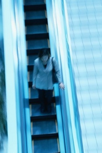 Businesswoman On Escalator : Stock Photo