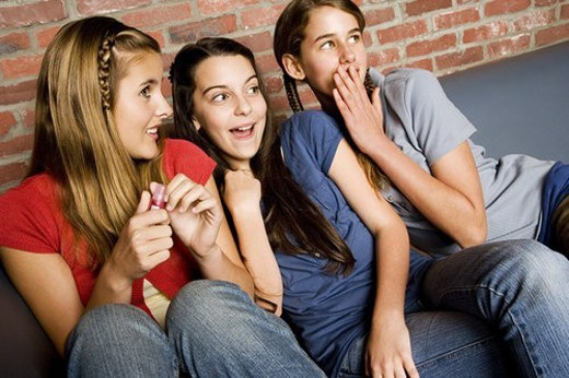 Stock Photo: 4029R-410566 Three teenage girls giggling at something out of shot