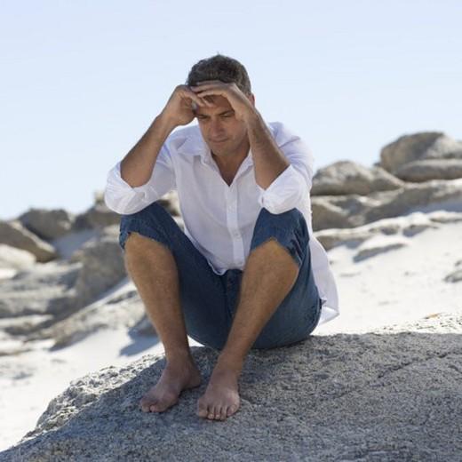 Stock Photo: 4029R-410736 A man sitting on rocks
