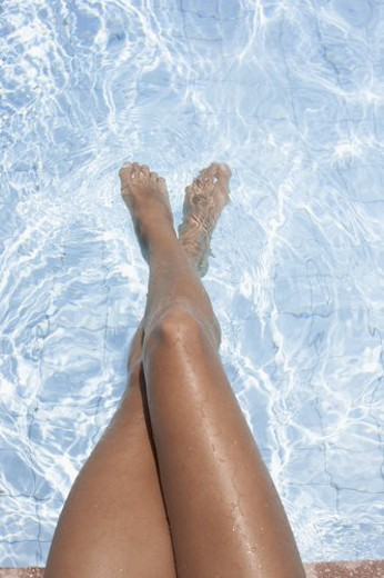 Woman s feet in water (focus on feet) : Stock Photo