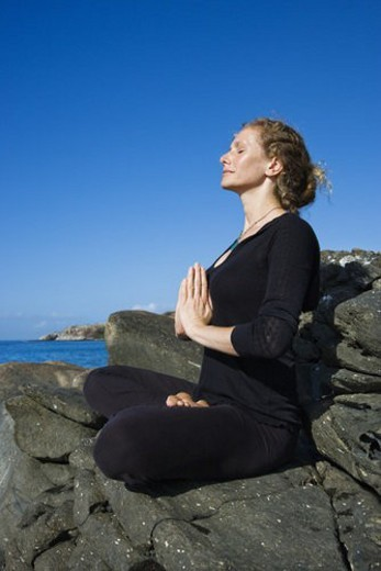Caucasian mid-adult woman practicing yoga on rocky coast of Maui, Hawaii. : Stock Photo