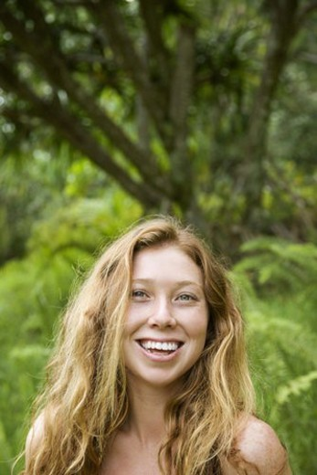 Stock Photo: 4029R-41499 Beautiful happy Caucasian young adult woman in lush forest smiling and looking at viewer.