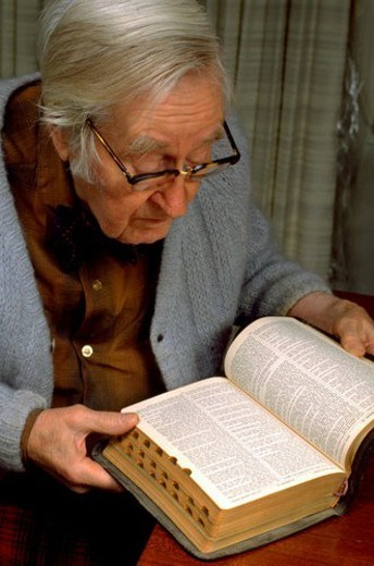 Retired physician age 86 reading Bible in his home : Stock Photo