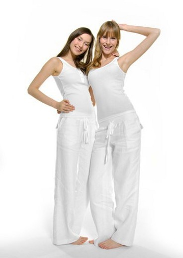 Portrait of two young women standing with their arms around and smiling : Stock Photo