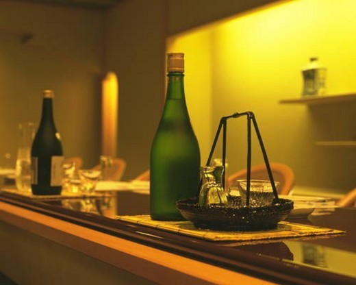 Stock Photo: 4029R-418242 Bottles of Sake and glasses on counter
